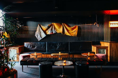 Interior of contemporary restaurant with stylish dark furniture and black walls in daylight
