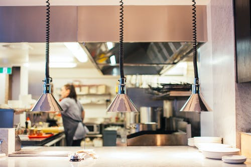 Side view of unrecognizable female chef in restaurant kitchen working behind counter with infrared lamps and serving kitchenware