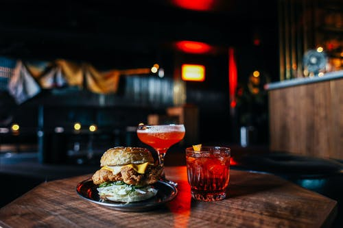 Delicious hamburger with cocktails on table