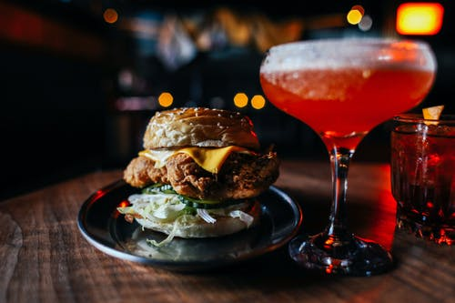 Appetizing hamburger with fried meat and lettuce served on wooden table with red alcoholic drink in modern cafe on blurred background