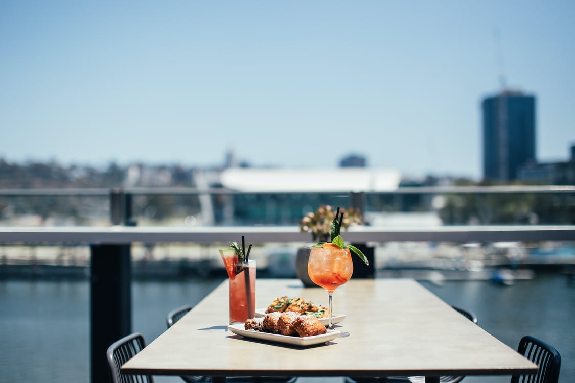 Delicious meat loaf served near colorful alcoholic cocktails on table on sunny terrace of cafeteria near river on blurred background
