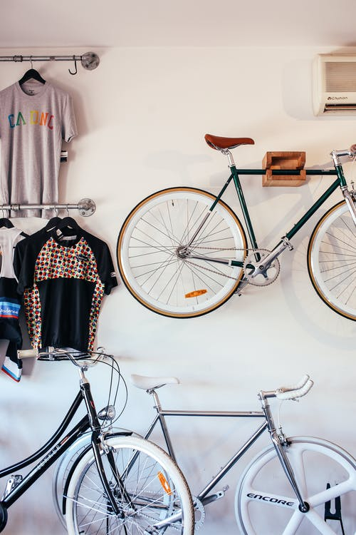 Bicycles at white wall with various t shirts hanging on hangers on metal racks in light room with transport in storage