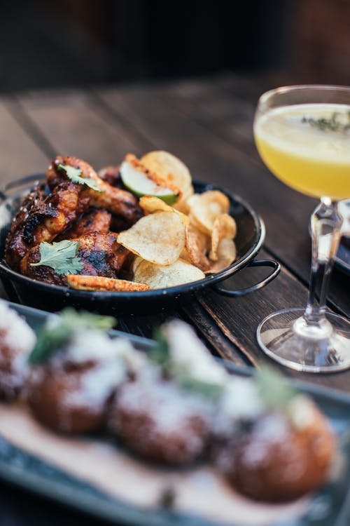 Tasty grilled chicken wings served with crispy chips on table with alcoholic beverage on table with blurred dish in cafe