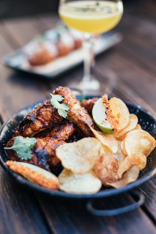 Grilled chicken wings with crisps decorated with herbs placed on wooden table with alcoholic cocktail on blurred background in restaurant