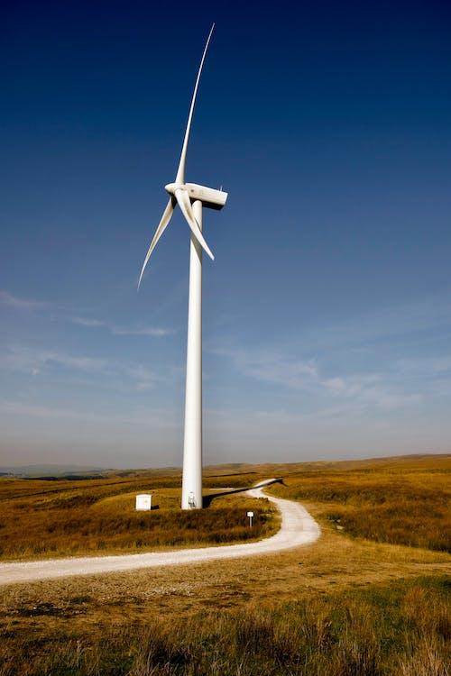 White Wind Turbine on Brown Field Under Blue Sky