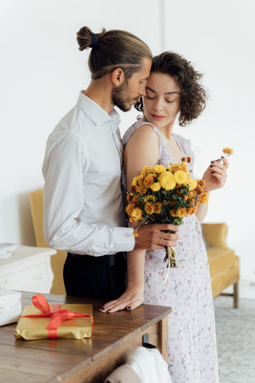 Man in White Dress Shirt Holding Bouquet of Flowers