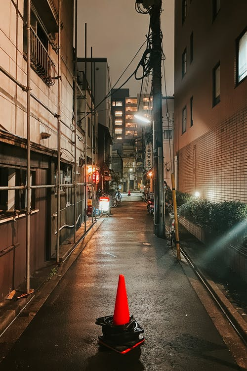 Traffic Cone In a Narrow Tokyo Alley