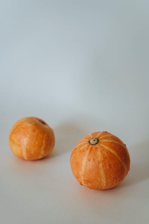 2 Orange Round Fruits on White Table