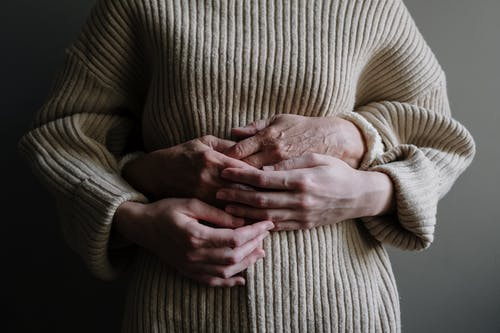 Woman in Brown Sweater Holding Baby
