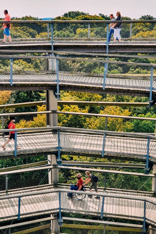 From above of unrecognizable group of tourists admiring greenery woods from old spiral observation tower