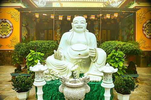 White Concrete Statue of a Man Near Potted Plants