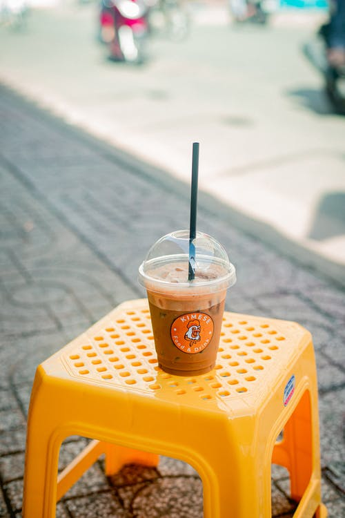 Clear Plastic Cup With Brown Liquid on Yellow Plastic Chair