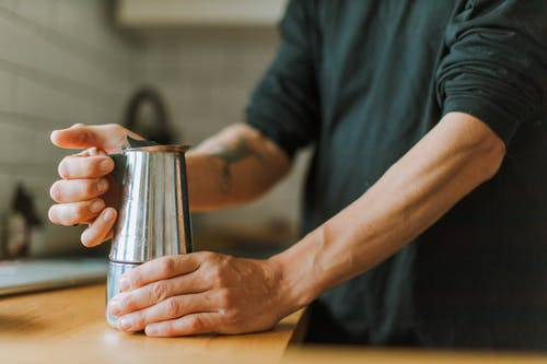 Person in Gray Shirt Holding Stainless Steel Cup