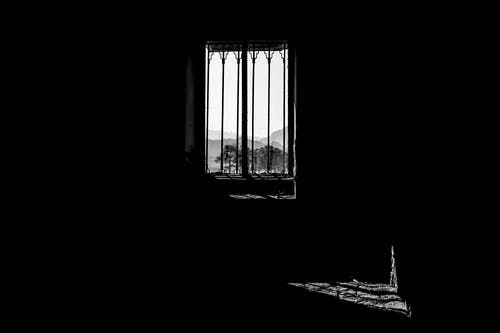 Grayscale Photo of Window Frame Casting Shadow