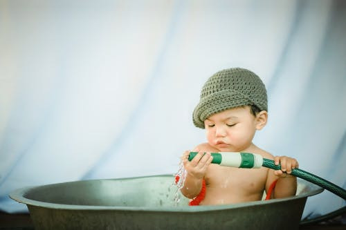 Charming baby boy looking closely at nozzle of garden hose while taking bath in old metal basin