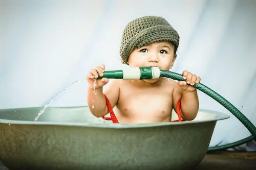 Cute little boy biting garden hose