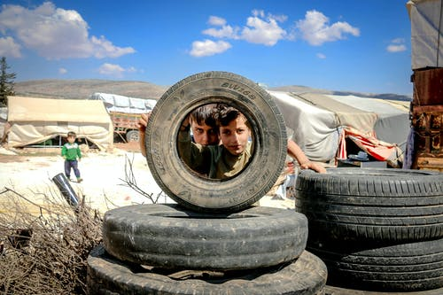 Pensive boys looking through big black wheel of vehicle under vibrant blue sky with clouds in encampment