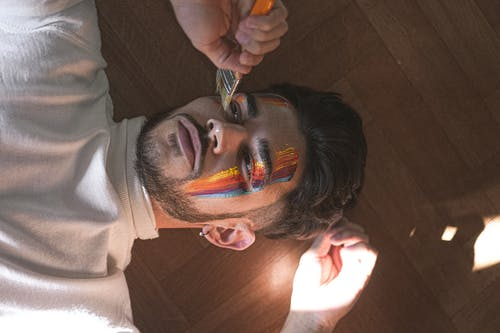From above young calm male painting bright multicolored lines on face by using paintbrush while lying on parquet and looking away pensively