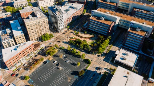 Drone view of cityscape with asphalt roads running between modern multistory buildings and parking area on sunny day