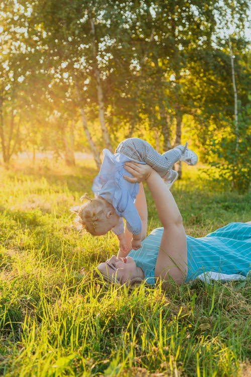 Side view of happy young woman in casual clothes lying on grassy lawn and playing with cute little baby while spending time together in park on sunny day