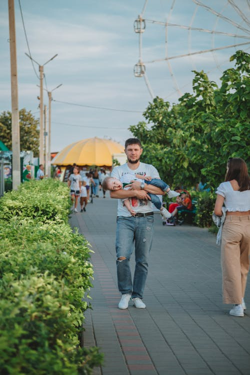 Full body of young man in casual clothes carrying funny little son on hands while walking on paved walkway in amusement park