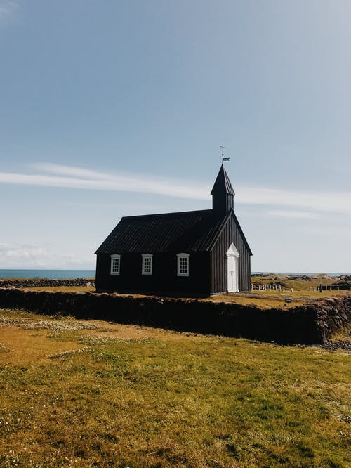 черно белый деревянный дом на поле зеленой травы под белыми облаками и голубым небом во время