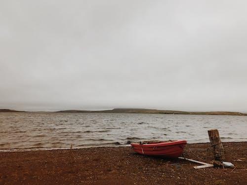 Красная лодка на коричневом песке у моря