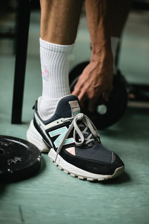 Crop sportsman legs in modern sneakers and socks near black weight plates and dumbbells