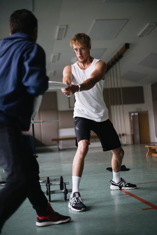 Sportsman with instructor training in gym
