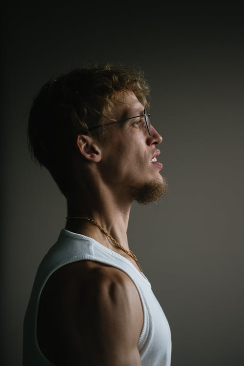 Side view of curly haired male with beard in glasses and chain standing against gray wall