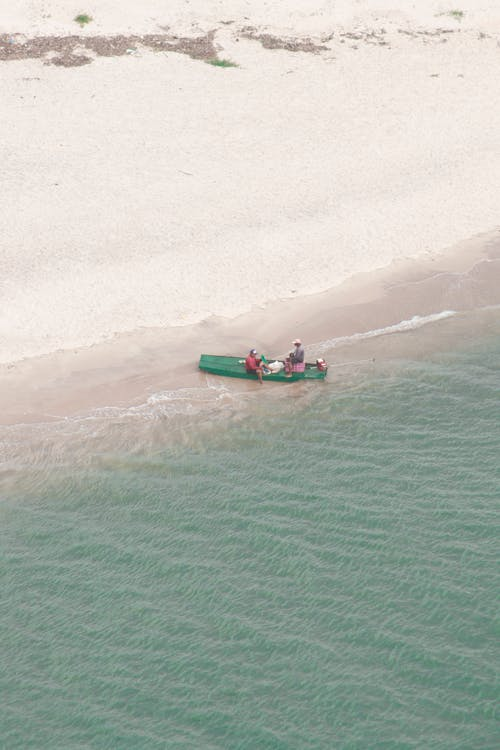 People Riding Red and Green Kayak on Sea