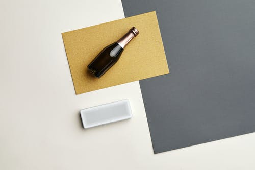 Black Glass Bottle on White and Brown Table