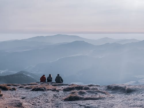 Back view of anonymous group of tourists admiring mounts near lake under cloudy sky at sundown