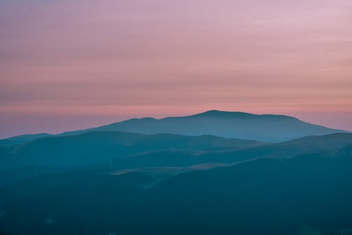 Foggy mountainous landscape under sunset sky