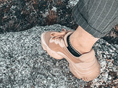 Crop faceless person leg in sneaker standing on stone