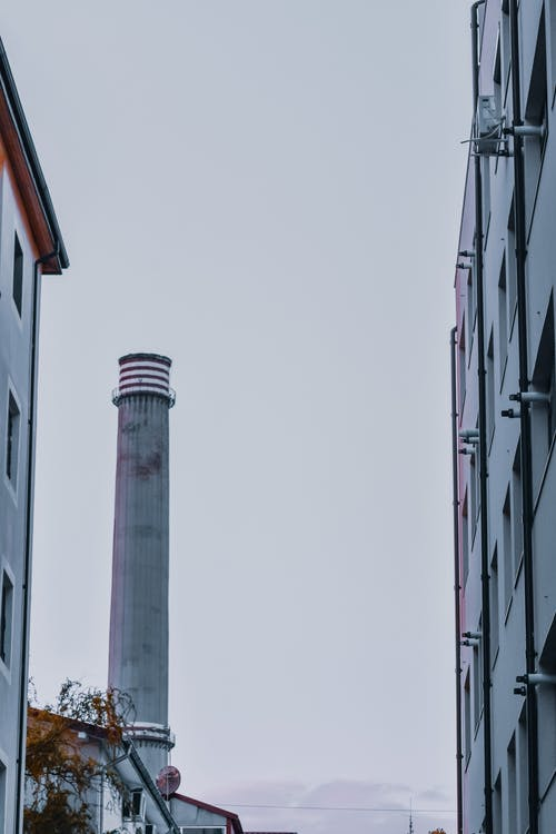 Low angle of tall smokestack pipe near simple buildings in industrial district against foggy sky