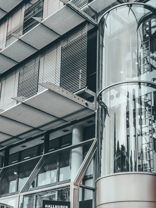 Long transparent cylindrical elevator and big simple ledges of tall multi storey construction in daytime
