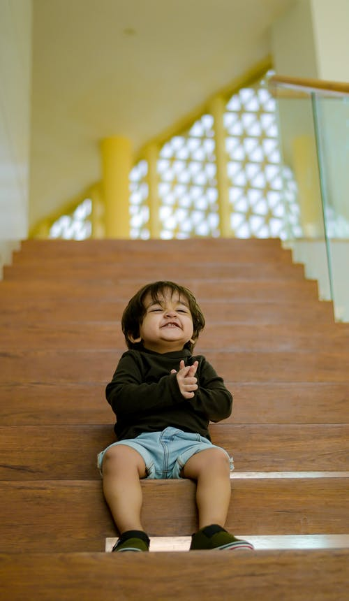 Cute little ethnic boy on stairs in building