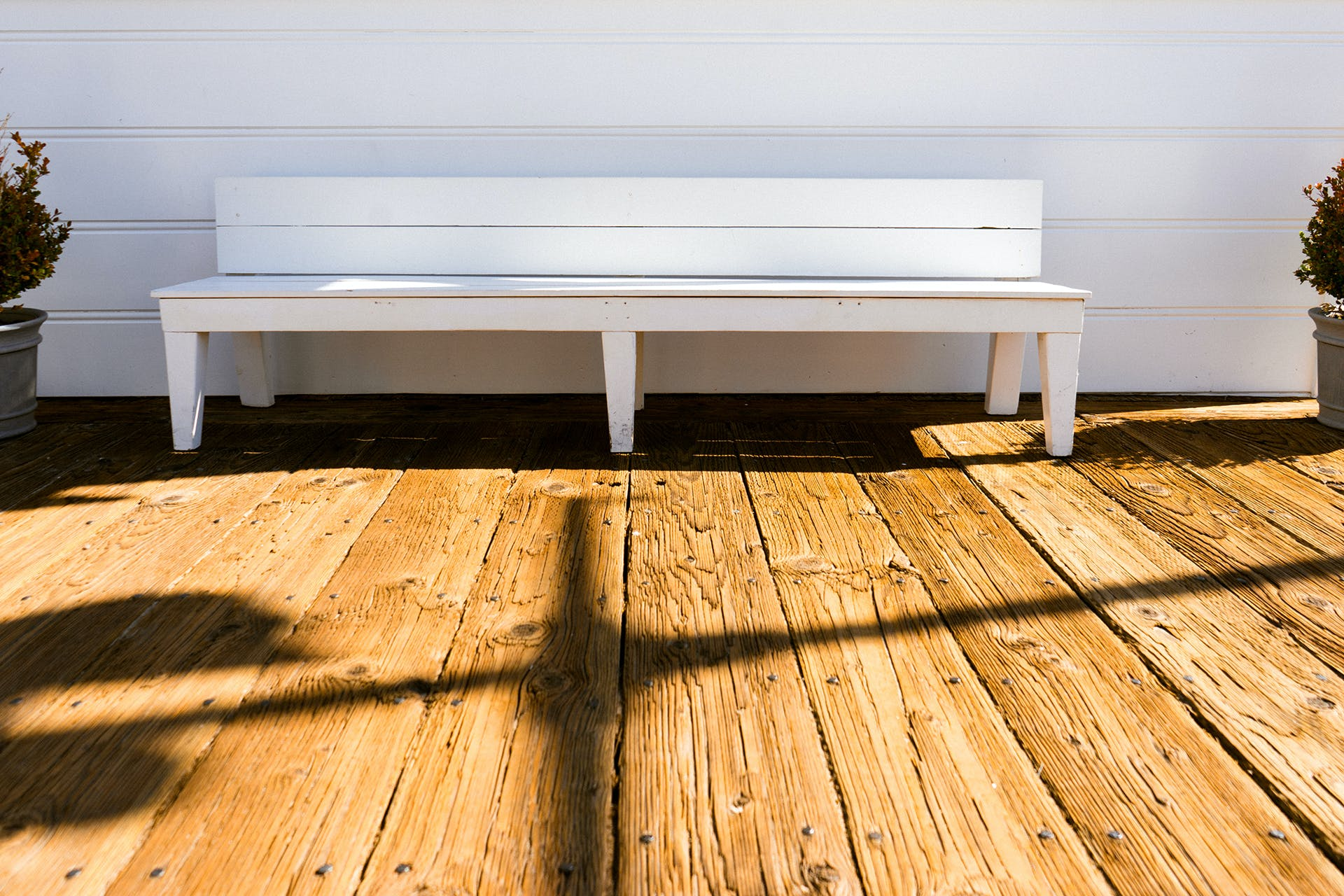 White Wooden Bench in Front of White Wall