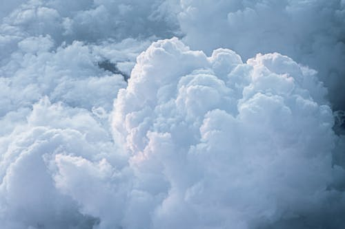 Thick dense white heavy clouds highlighted with sun in sky in overcast sky in daytime
