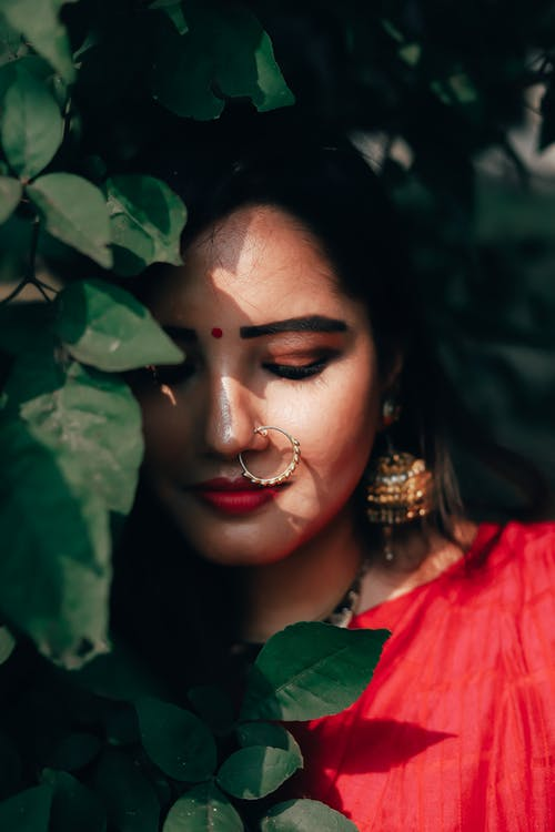 Ethnic female with bindi and massive earrings looking down near lush leaves of green bush
