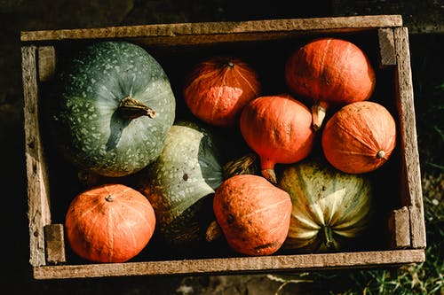 Orange and Green Pumpkins in a Wooden Crate