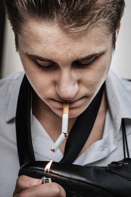 Man Lighting Broken Cigarette