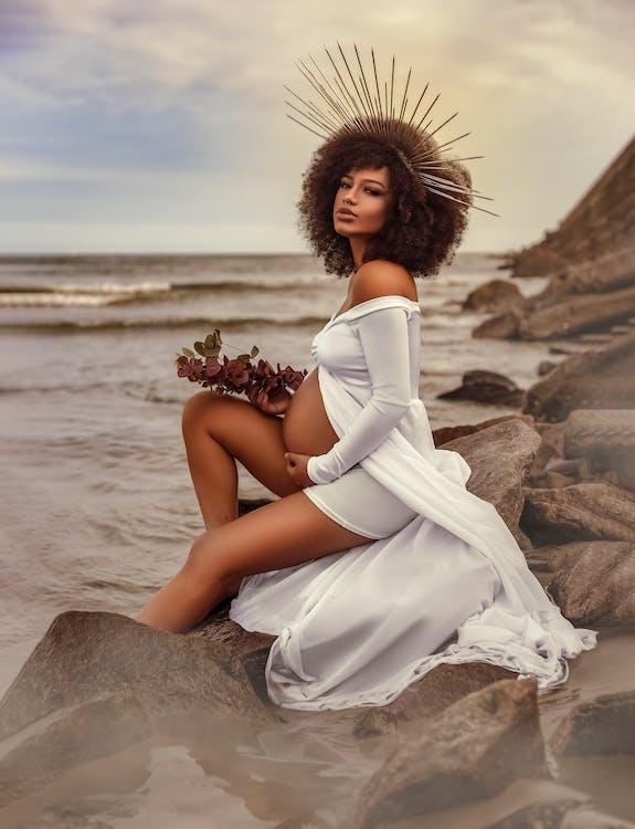 Woman in White Dress Sitting on Brown Rock Near Sea