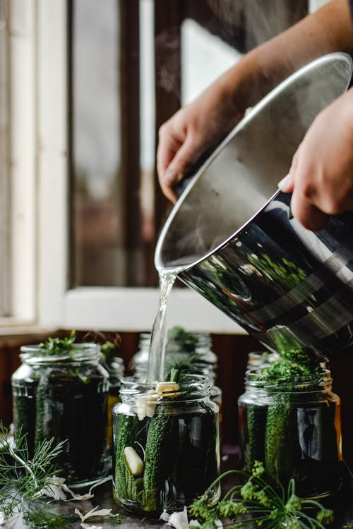 Person Pouring Water on Pickled Cucumber Jars