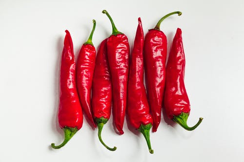 Red Chili Peppers on White Surface