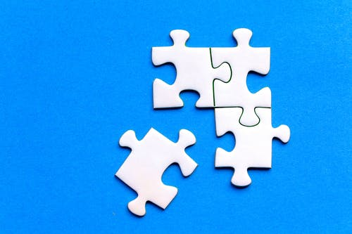 White Puzzle Pieces on Blue Surface