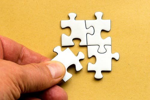 Person Holding White Puzzle Pieces