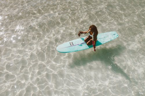 Woman in Red and Black Wetsuit Holding White Surfboard on Beach