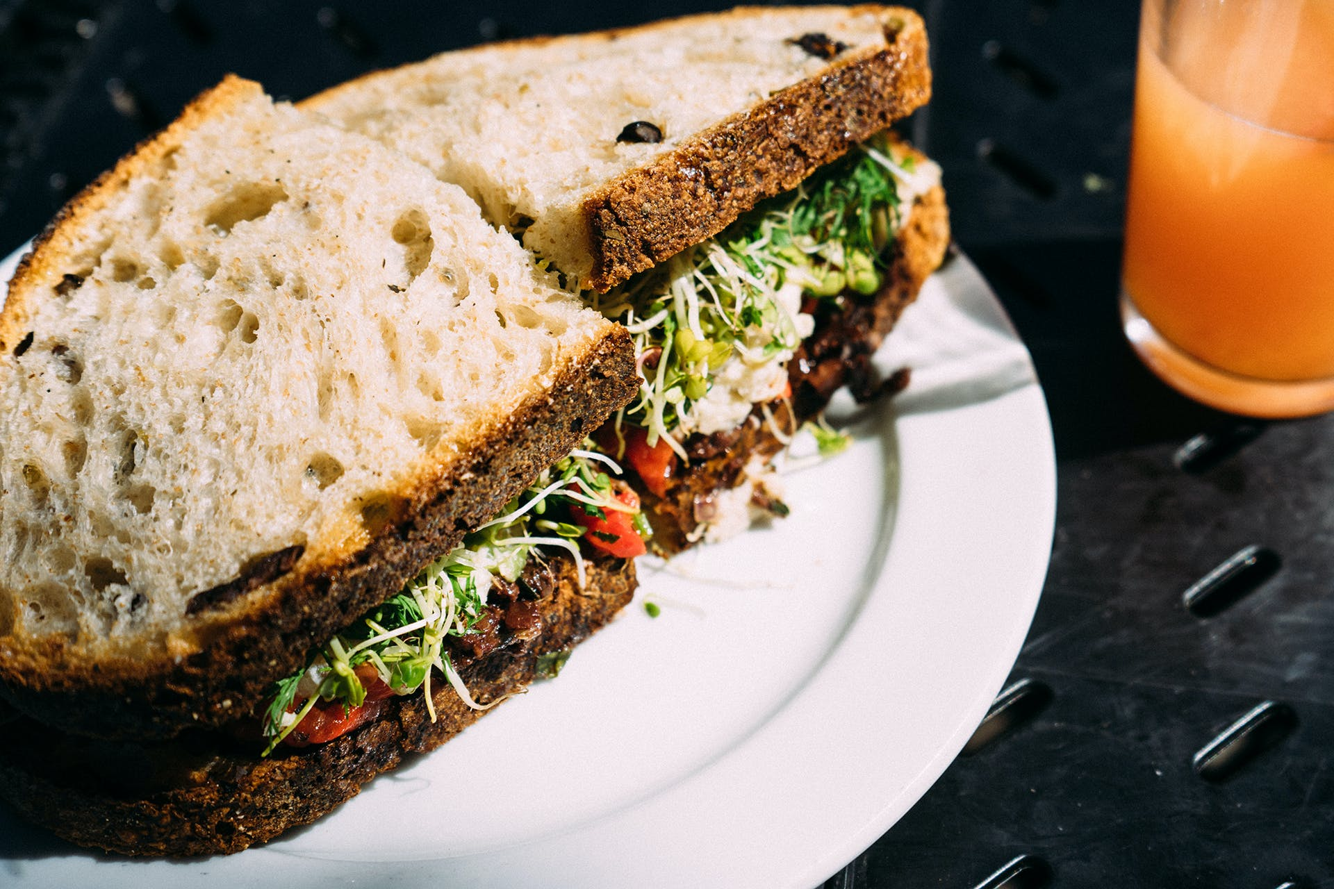 Vegetable Sandwich on Ceramic Plate Near Drinking Glass